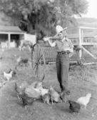 Young woman dressed as a farmer bringing food to the chicken — Stock Photo