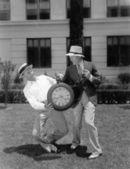 Zwei männer ringen mit einer überdimensionalen taschenuhr — Stockfoto