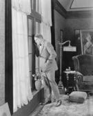 Adam pencereden dışarı bakarak bir oturma odasında — Stok fotoğraf