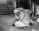 Jonge vrouw zit een haard warped in een bont deken op zoek triest — Stockfoto