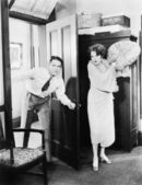 Woman standing behind a door trying to hit a man with a pillow — Stock Photo