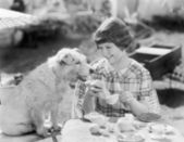 Girl and her dog having a picnic — Stock Photo