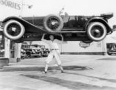 Strong man lifting a car over his head — Stockfoto