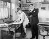 Dois homens de pé em um escritório, um passando suas calças — Foto Stock