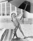 Garota colocando um grande guarda-chuva para a areia — Foto Stock