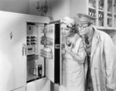 Man and woman standing in front of a refrigerator — Stock fotografie