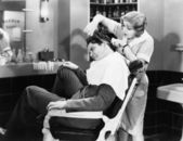 Woman barber cutting a man's hair — Stock Photo