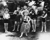 Group of children performing with instruments and one girl dancing the hula — Stock Photo