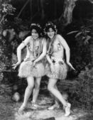 Two women dancing in grass skirts — Stock Photo