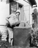 молодая женщина, сдачи мусор в мусорный — Стоковое фото