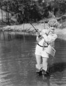 Junge frau mit wathosen holding eine angelrute — Stockfoto