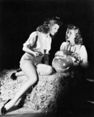 Two women sitting on a bale of hay carving a pumpkin — Stock Photo