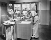 Two surgeons and a nurse in the scrub room preparing for an operation — Stockfoto