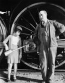 Little girl with an oil can standing next to a locomotive and the engine driver — Stock Photo