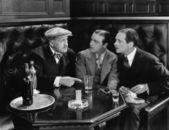 Tres hombres sentados juntos en un bar — Foto de Stock
