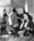 Two women working on a phone bank — Stock Photo