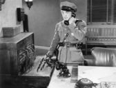 Officer talking on a telephone next to a switchboard — Stock Photo