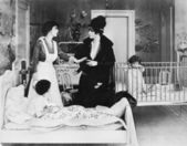A woman with her nanny and two children in a bedroom talking with each other — Stok fotoğraf