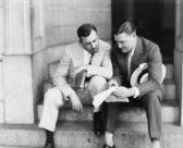 Dva muži sedí na schodech a čtení dokumentu — Stock fotografie
