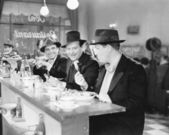 Three men sitting at the counter of a diner — Stock Photo
