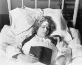 年轻女子躺在床上睡觉,拿一本书 — 图库照片