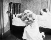 Nurse praying for an outlaw lying in bed — Stock Photo