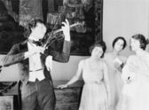 Three young women looking with adoration at a violin player — Stok fotoğraf
