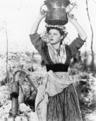 Молодая женщина с ведро воды на голову рядом с хорошо — Стоковое фото