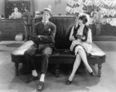 Donna guarda un uomo addormentato su un divano in pelle — Foto Stock