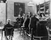 Men sitting around a counter in a bar — Stockfoto