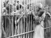 One woman standing in front of a jail talking with a group of women — Stock Photo