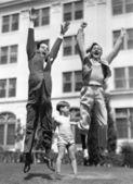 A little boy pretending to lift two grown men — Stock Photo