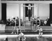 Young woman standing on a diving board surrounded by a group of playing — Stockfoto