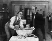 Two men giving a baby a bath — Stock Photo