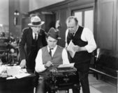 Three men in an office hunched over a typewriter — Foto de Stock