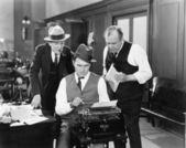 Tre män i ett kontor böjd över en skrivmaskin — Stockfoto