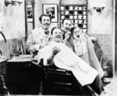 Group of four men at a barber shop singing — Stock Photo