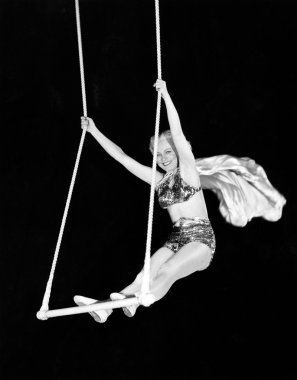Portrait of a female circus performer performing on a trapeze bar