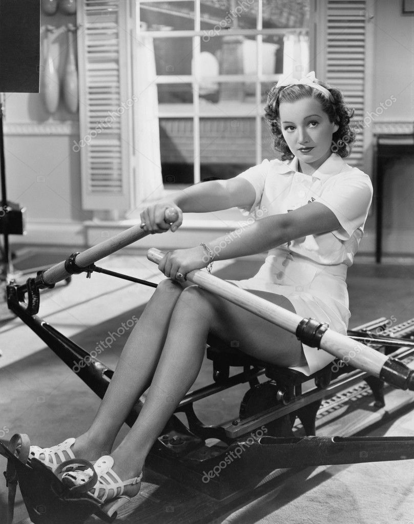 Woman using rowing machine — Stok fotoğraf #12290089