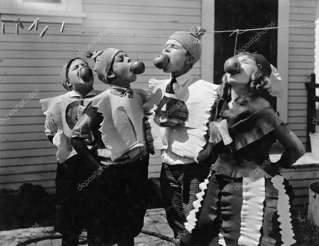 Kids biting apples on strings at Halloween — Stock Photo #12292720