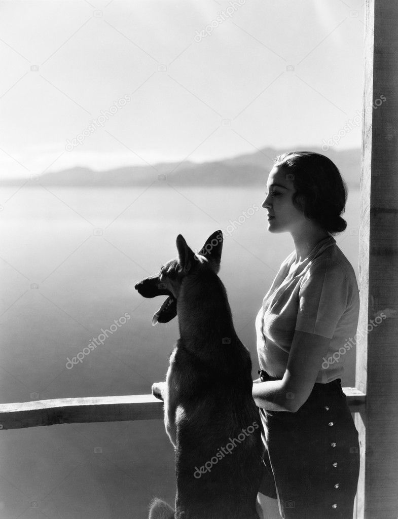 Woman and dog looking out over water — Stock Photo #12293263
