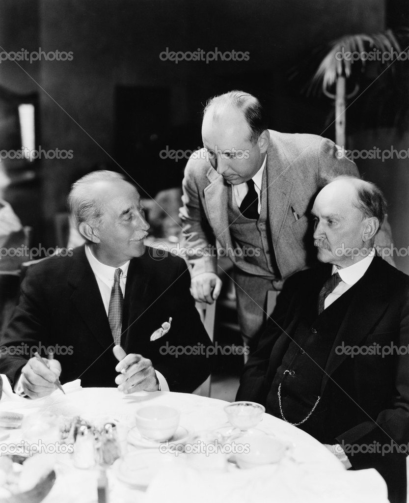 Three men sitting together at a table  Stock Photo #12293468