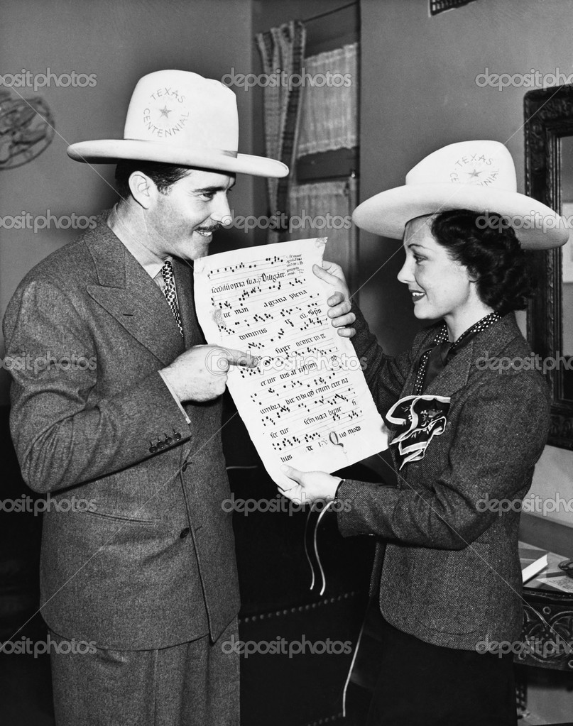 Couple with cowboy hats looking at sheet music — Stock Photo #12293499