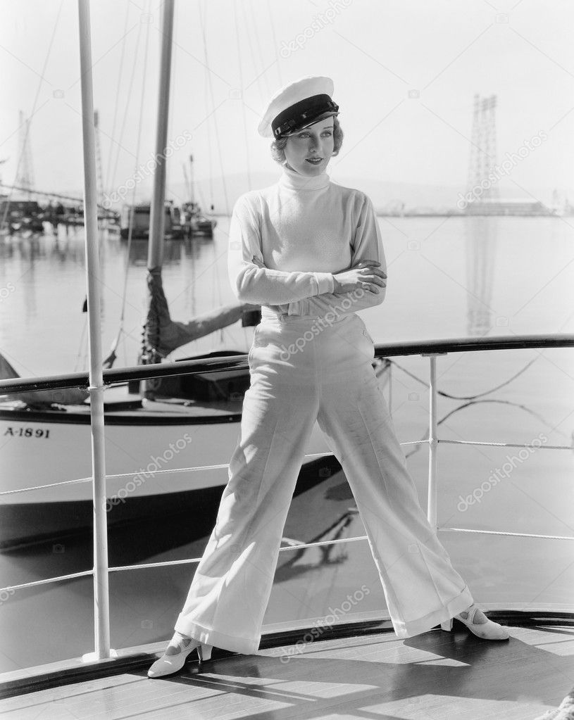 Woman in a captains hat standing on top of a sailboat  Stock Photo #12294423