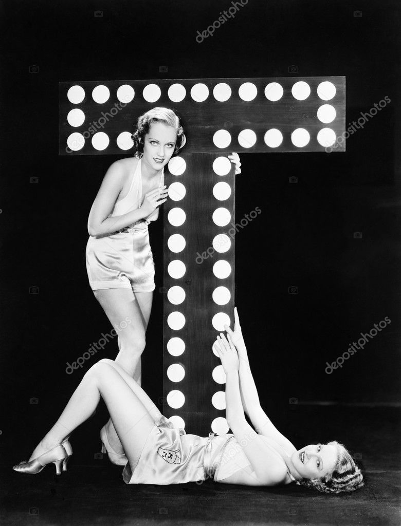 Two young women posing with the letter T — Stock Photo #12294634