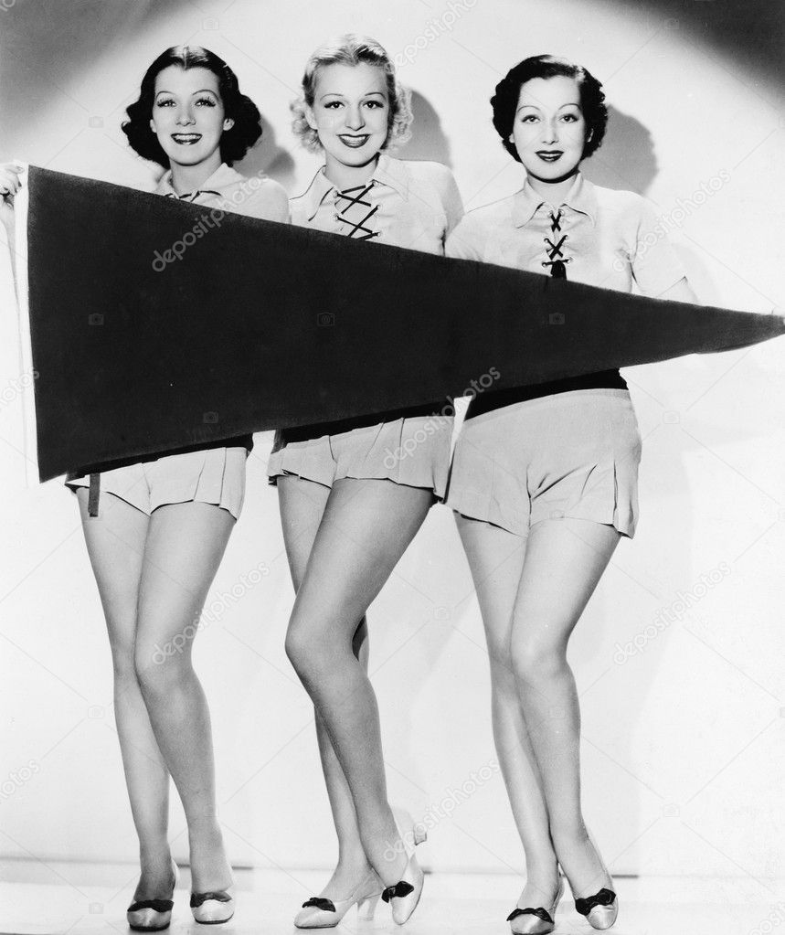 Portrait of three young women holding a banner and smiling — Stock fotografie #12294656