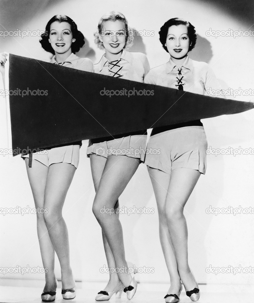 Portrait of three young women holding a banner and smiling — Photo #12294656