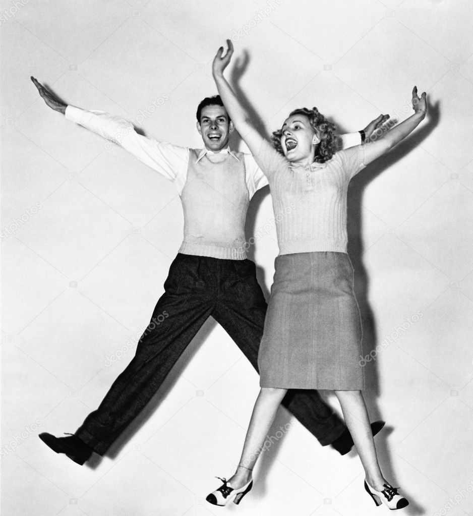 Couple jumping with their arms outstretched  Photo #12294669