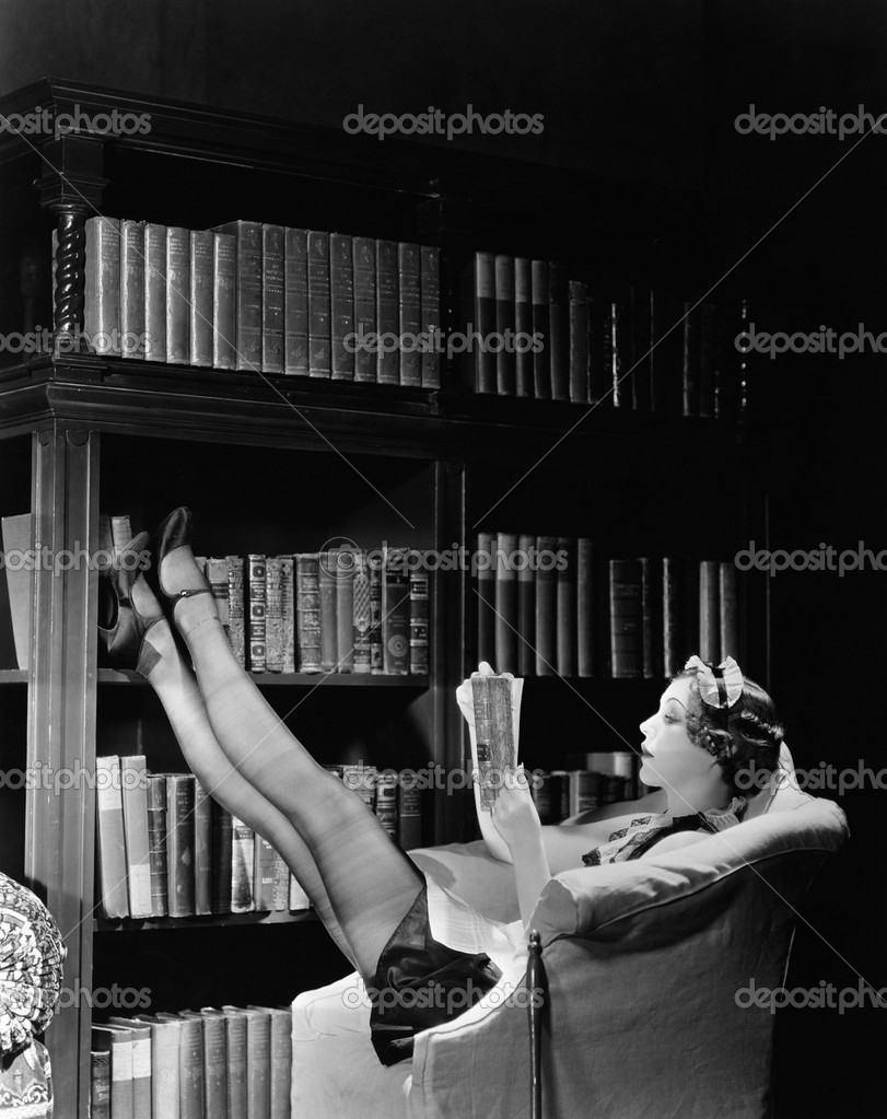 Young housekeeper reading a book while reclining in a library armchair — Foto Stock #12294671