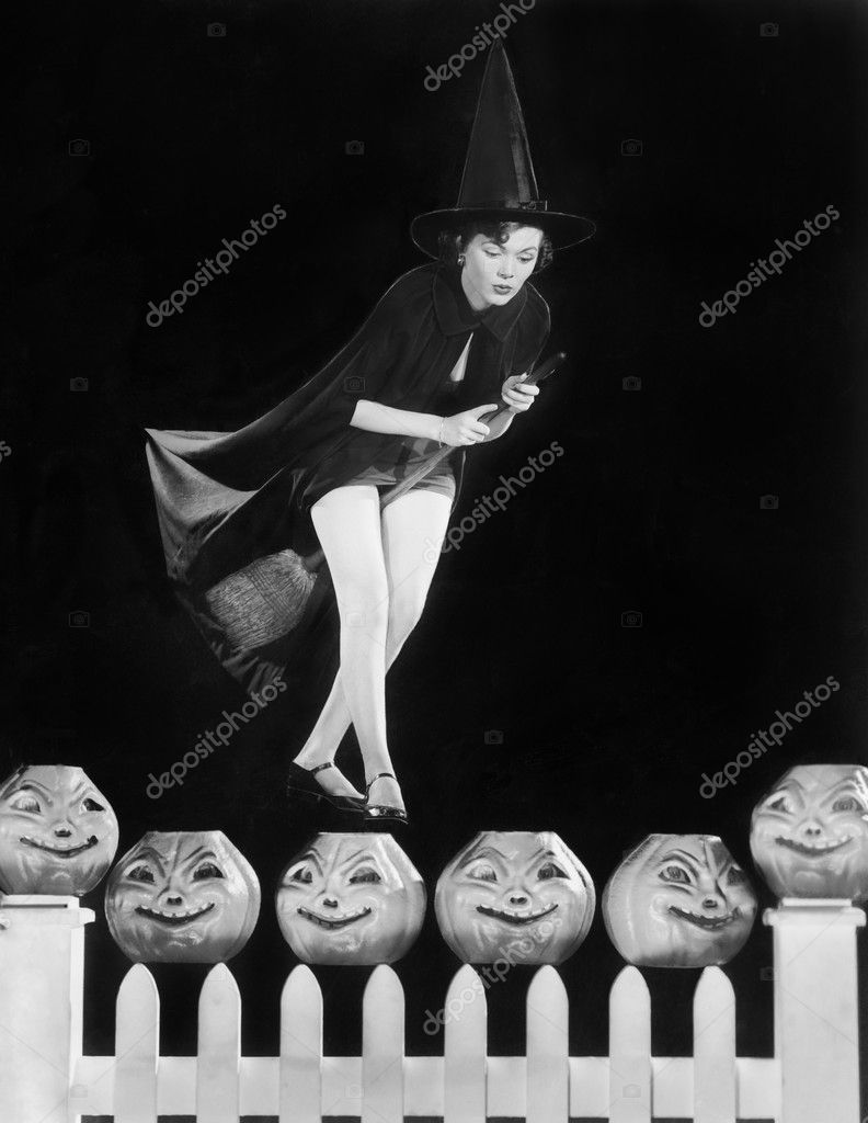 Young witch hovers on her broom, eyeing which pumpkin to choose — Stock Photo #12297514